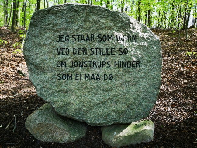 "Mindesten i skoven, med tekst: ""Jeg Staar som værn ved den stille sø om Jonstrups minder som Ei maa dø"""
