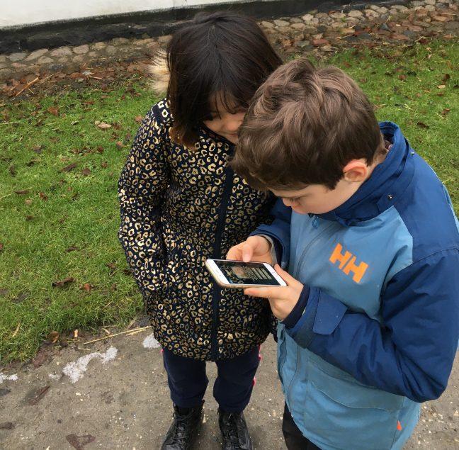 To børn kigger på mobiltelefon