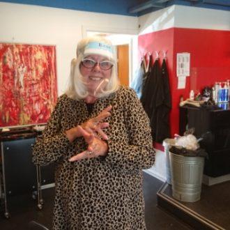 Dame i frisørsalon med visir