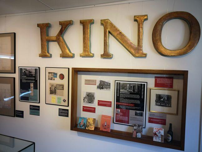 Guldbogstaver KINO og montre på væg