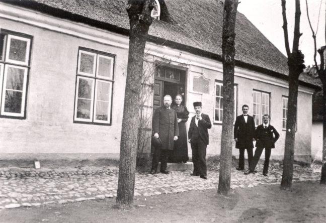 Mænd i sort tøj foran lyst hus