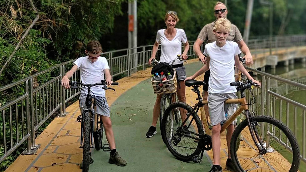 Family cycling on bamboo bikes in Bangkok.