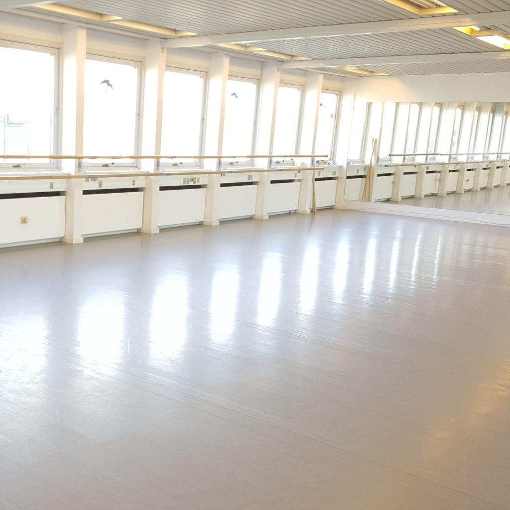 Balletsalen. Vores store 160 kvm lyse balletsal, med spejlvæg, balletbarre og vinduer på dette sider.