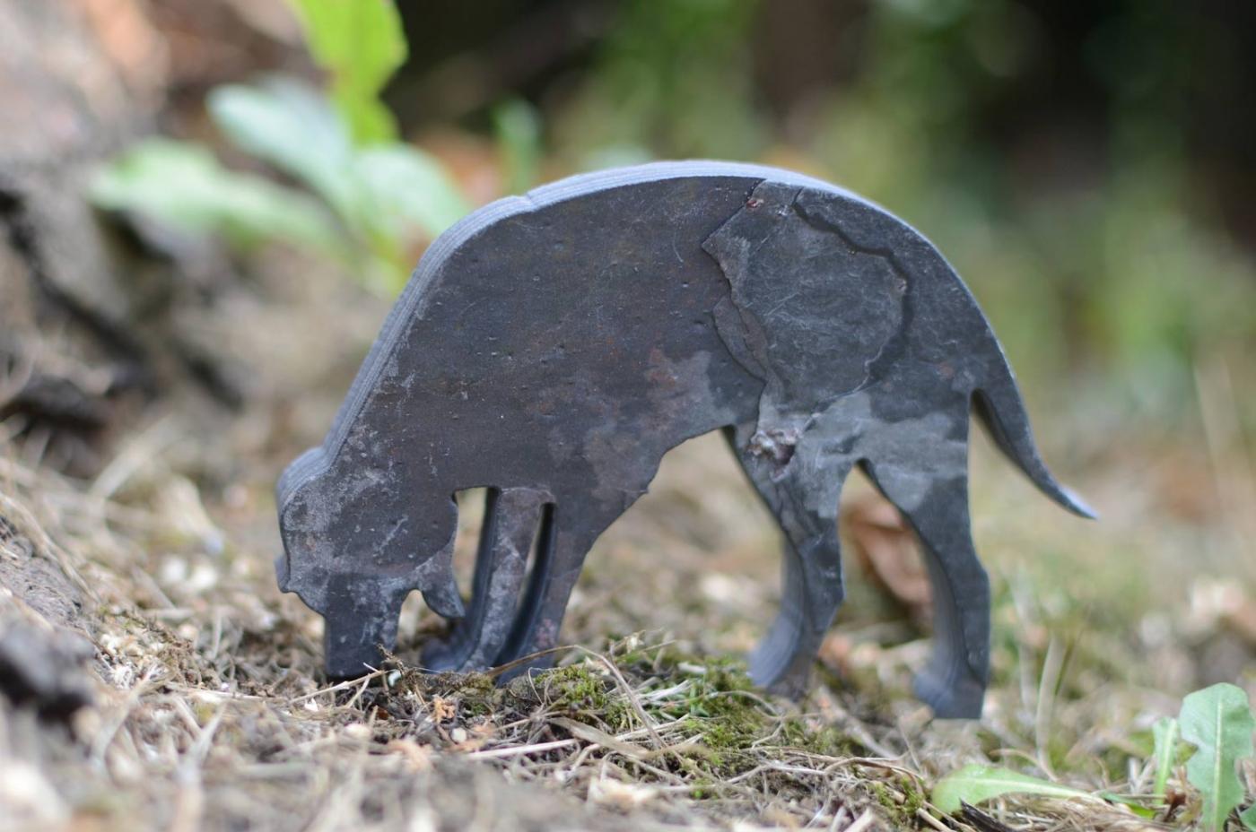 A small slate dog, palm sized.