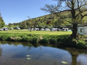 The touring pitch at Parc Farm Caravan Park viewed from across the river.