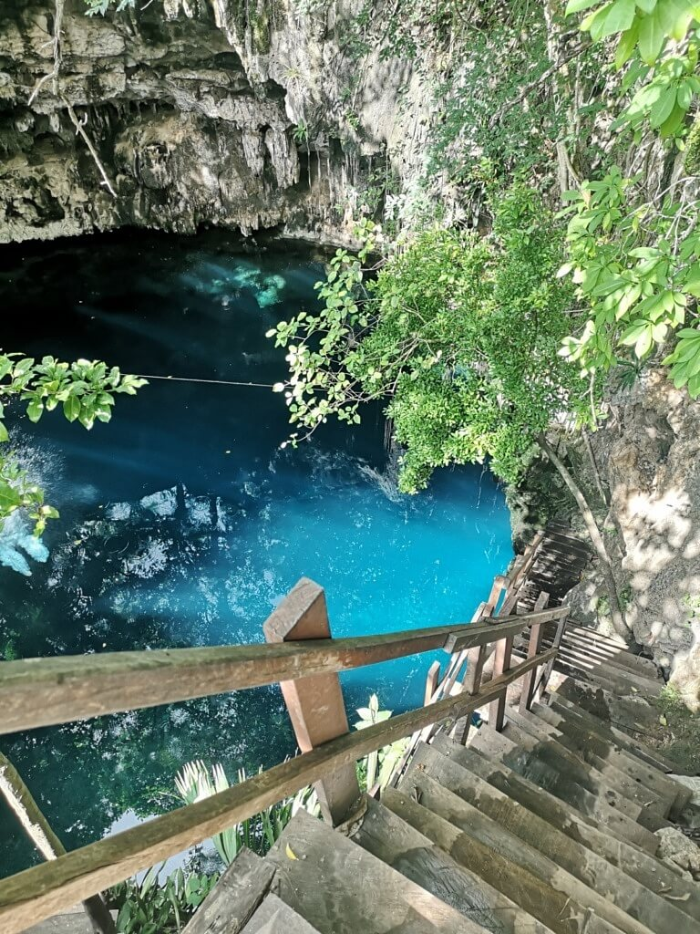 a ladder leading down to azure water of cenote near Merida