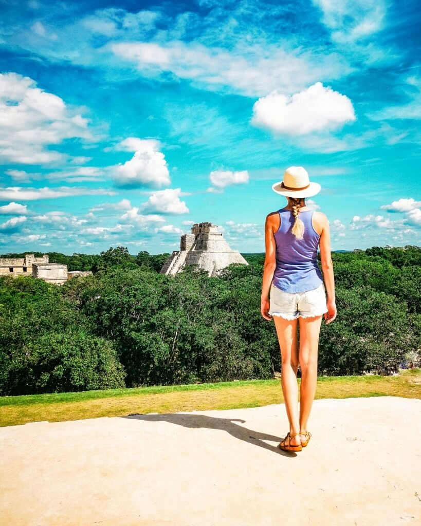 Girl watching Uxmal Mayan Ruins hidden in the jungle