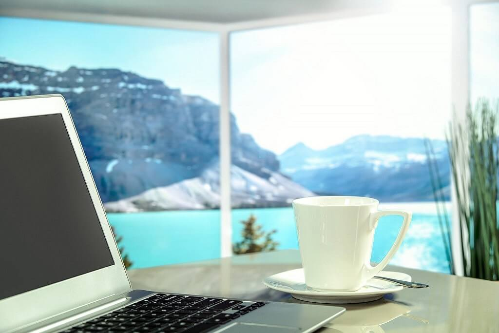 A laptop and a cup of coffee in with beautiful view