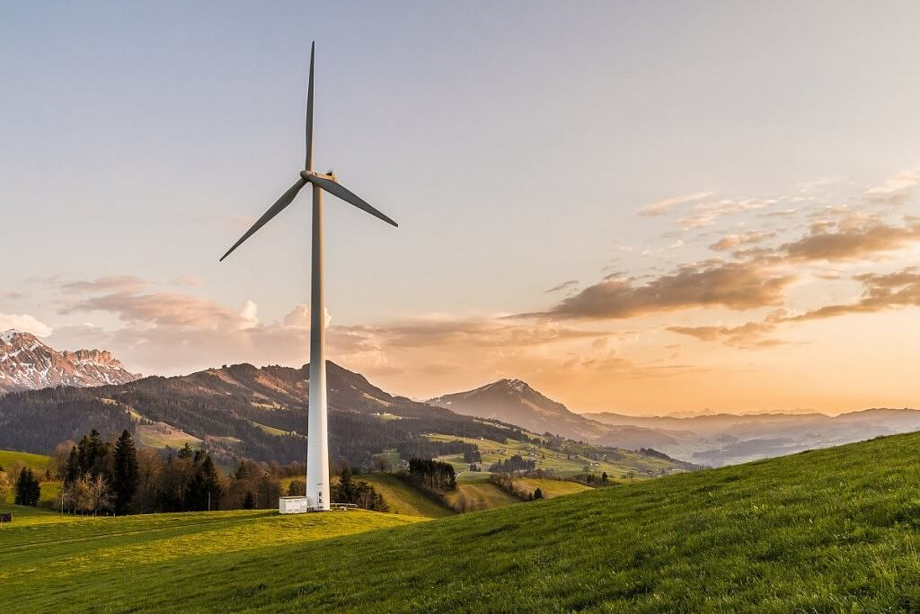 windmill in a green field producing alternative-energy