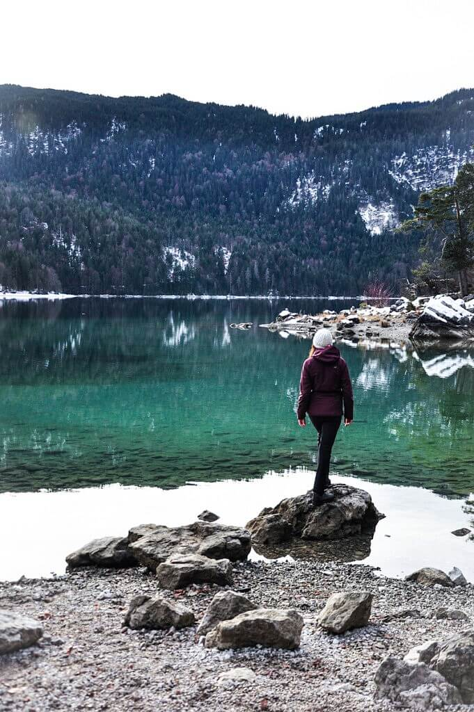 A girl standing on the shores of lake Eibsee
