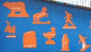 A. Siekmann. Die Umrisse von Figuren aus verschiedenen Städten auf einem Abfallcontainer