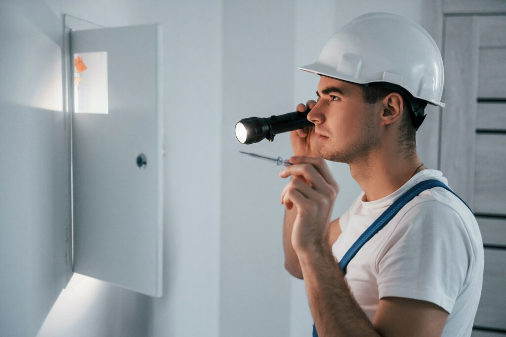 Young male electrician in white hard hat works indoors in the room