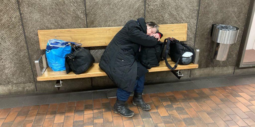 Hemlös kvinna vilar på tunnelbanestation