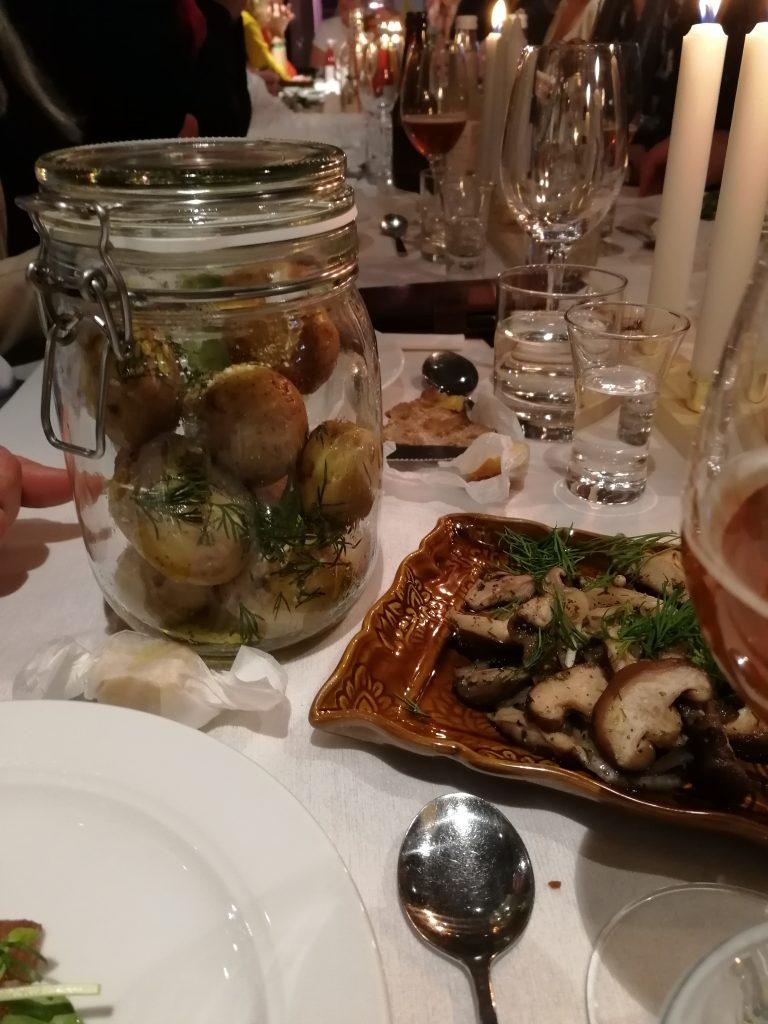 Potatis i glasburk och svamp på brun tallrik i en vacker dukning på Glocal dinner