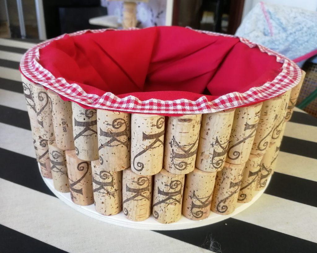 Rund brödkorg gjord av vinkorkar med rött foder och rödrutiga kanter.