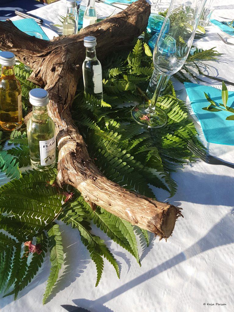 Ormbunke, trästock passar fint med snapsflaskor och vinglas på bordet