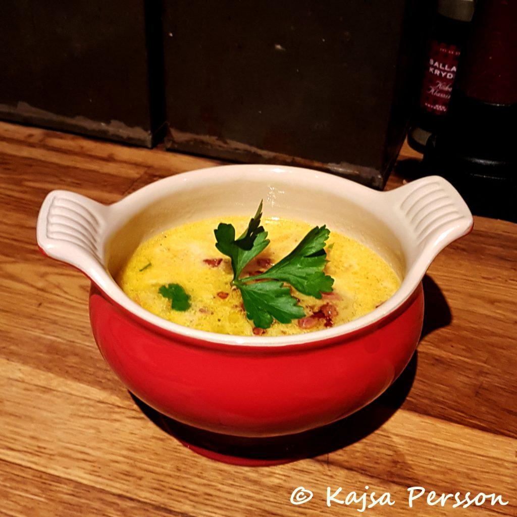 Röd soppskål med soppa. Soppan är gul och ovanpå finns det klippt Koriander i grönt. Soppa till middag