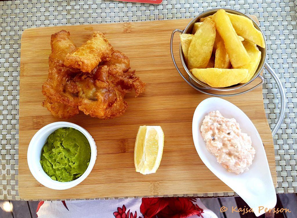 Fish & Chips på en träbricka med grön ärtpure som tillbehör