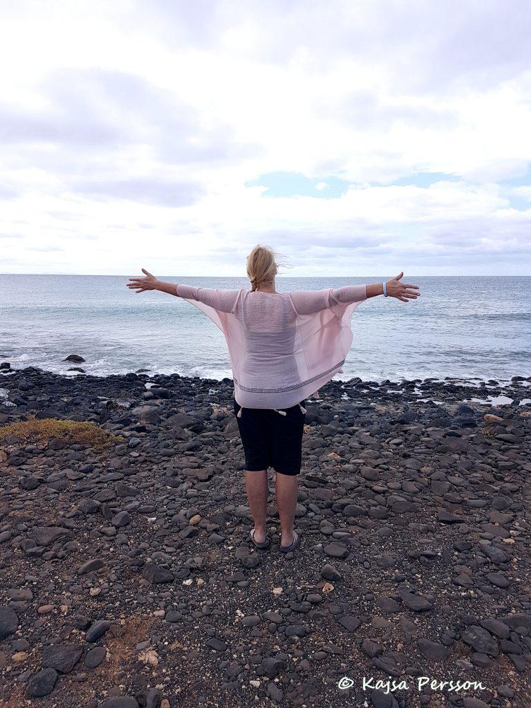 Kvinna vänd mot havet, sträcker ut händerna åt sidan. Den rosa sjalen fladdrar i vinden.