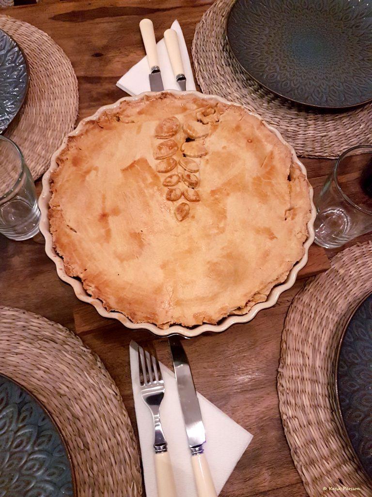 Dukning med en pajform mitt på bordet. Pajtäcker är dekorerat med en bladranka.