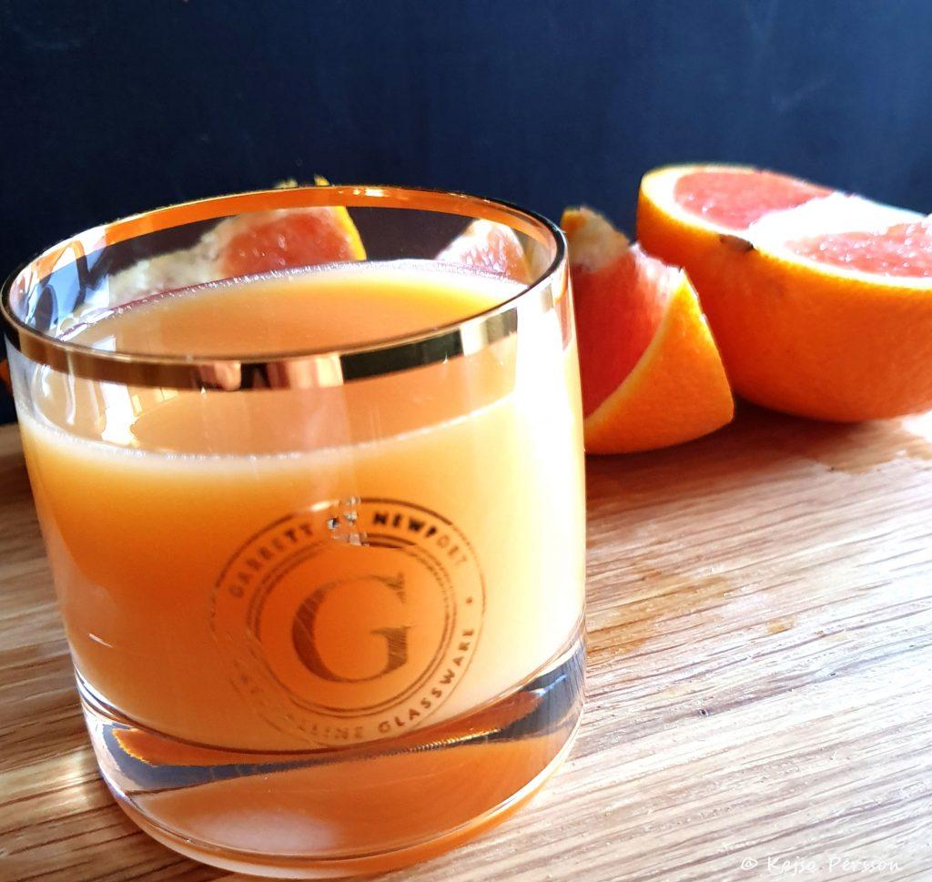 Litet glas med guldkant och guldekor med orangea juice på en skärbräda. Bakom ligger en delad blodapelsin i klyftor