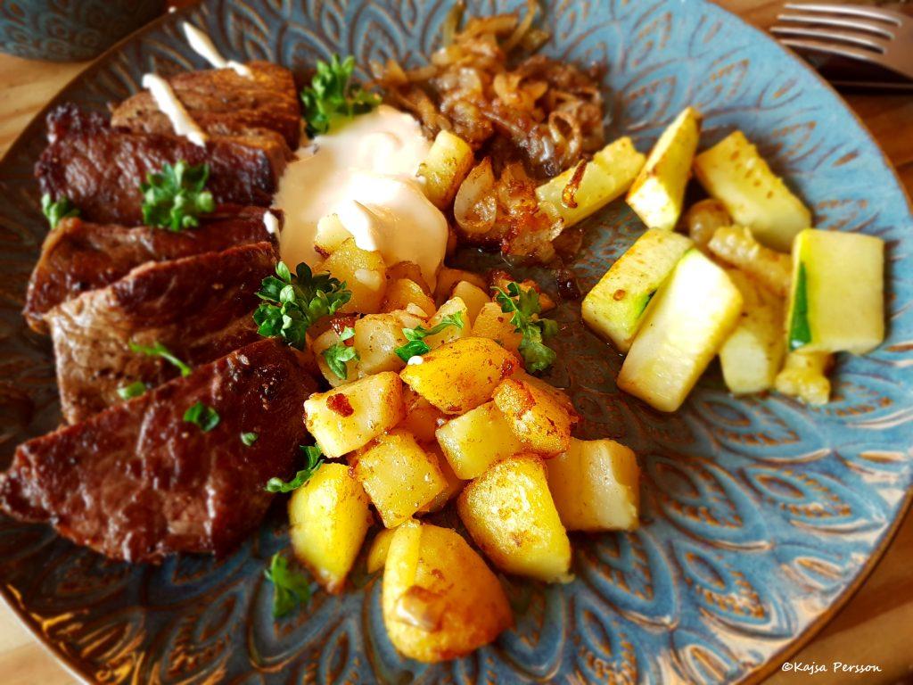 Biff Rydberg middag med stekt potatis, brynt lök och senapscréme. Middagen ligger upplagd på en blå tallrik.