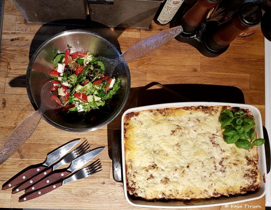 Lasange i en ugnsform, bestick och sallad i skål på köksbänken.