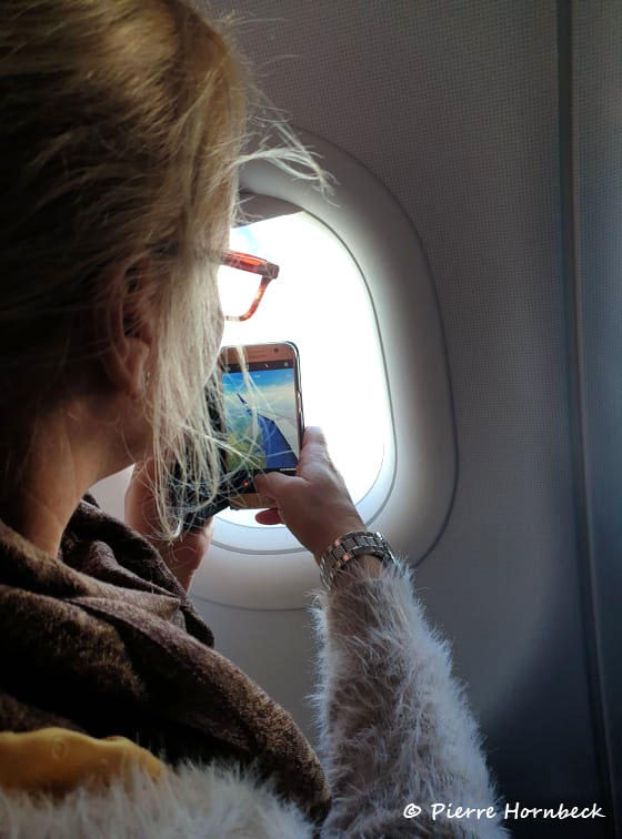 Tjej tar foto med sin mobiltelefon genom flygplansfönster