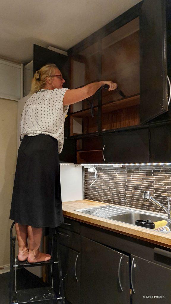Tjej Ångtvättar köksskåp för att få bort ohyra i köket