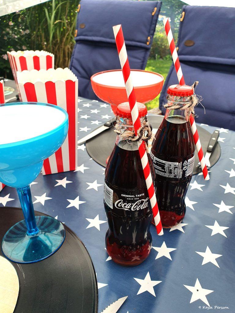 Coca cola i glasflaskor med röd randiga sugrör fastknutna runt halsen och rödrandiga popcornshållare