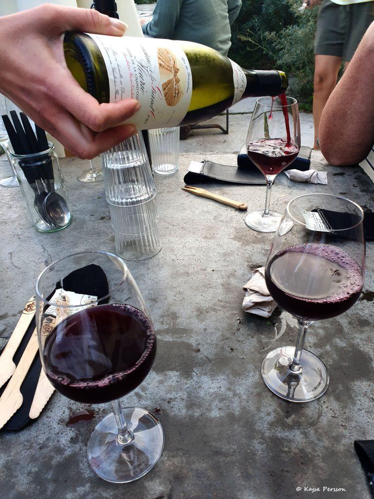 En hand håller i en flaska rött vin samtidigt som den fyller på ett glas. Två glas har redan rött vin i sig.