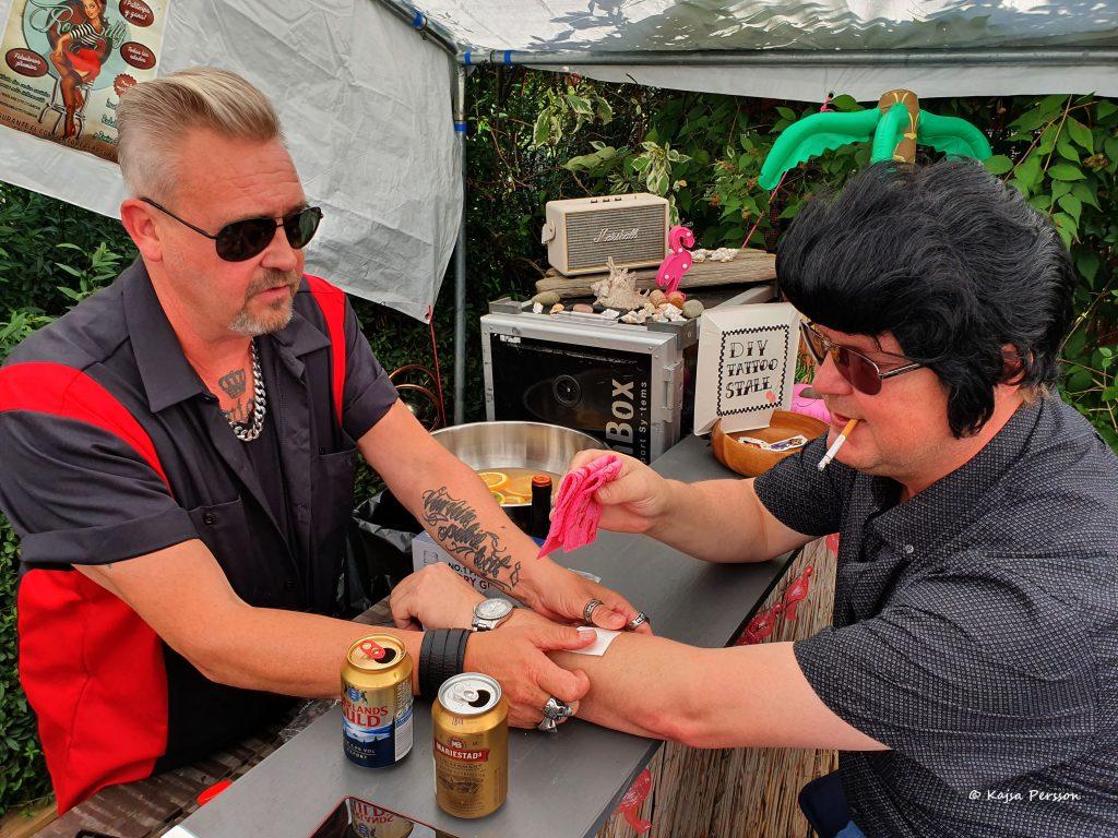 En kille hjälper en annan kille med Elvisfrisyr med en gnuggis tatuering
