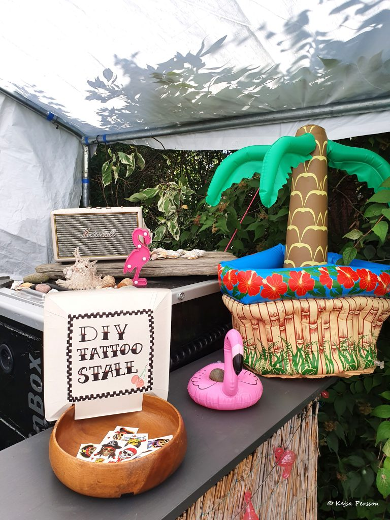 En skål med gnuggisar och en skylt att man kan göra det själv, en högtalare och en upplåst palm