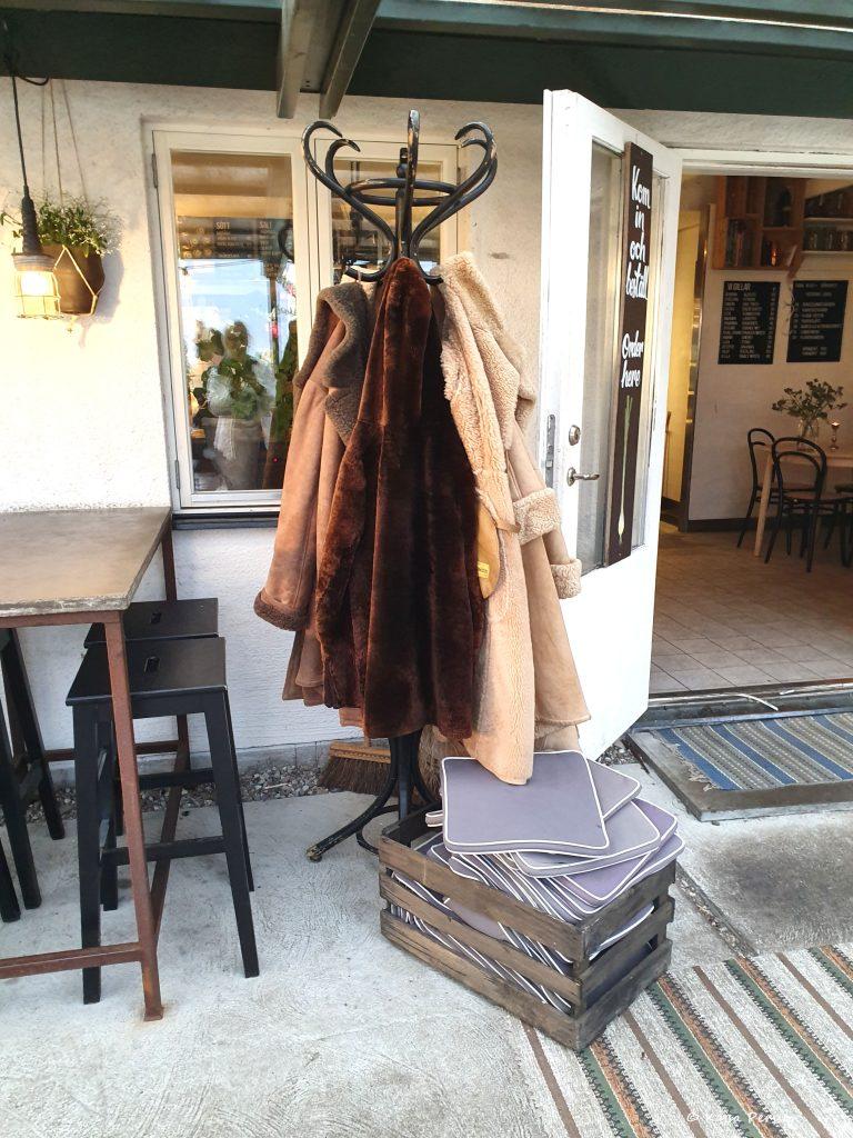 Pälsjackor på en majortambur vid sidan om ingång till restaurangen. Det blåser frfiska vinda vid Hörte Brygga