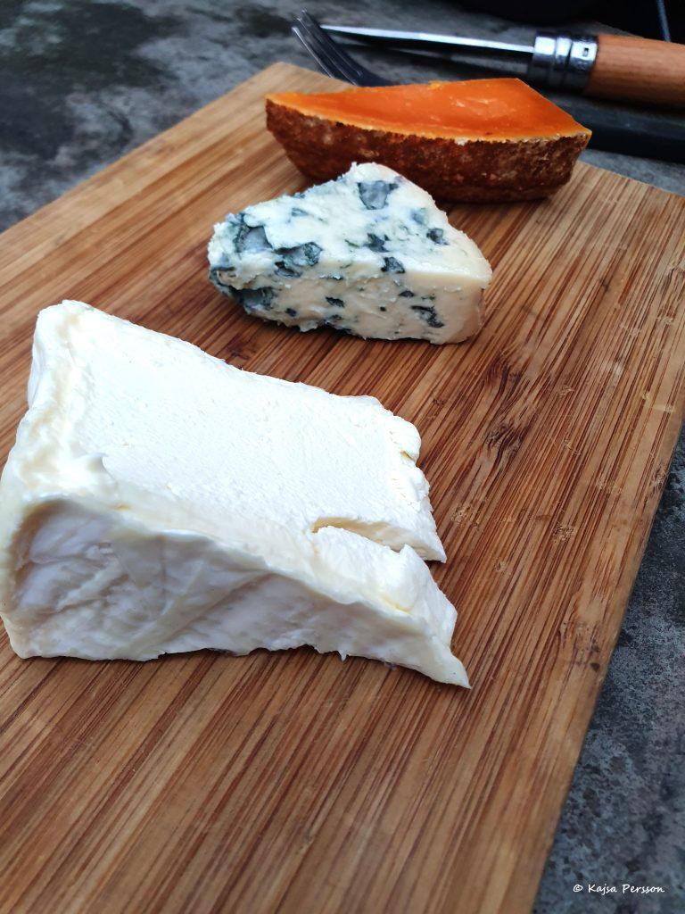 Ek Skärbräda med tre olika ostar. En brieost, en mögelost och en orange fast ost