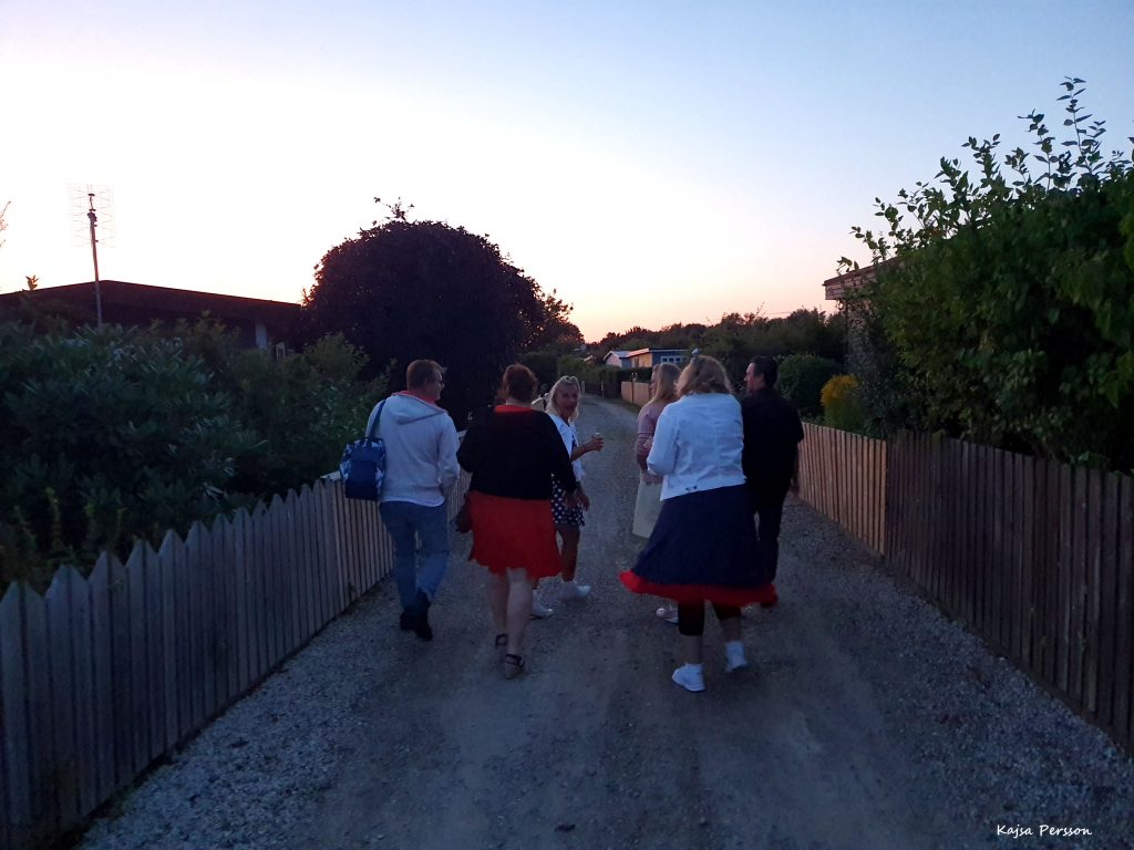 Personer på en grusgång en sommarkväll, på väg till dansbanan