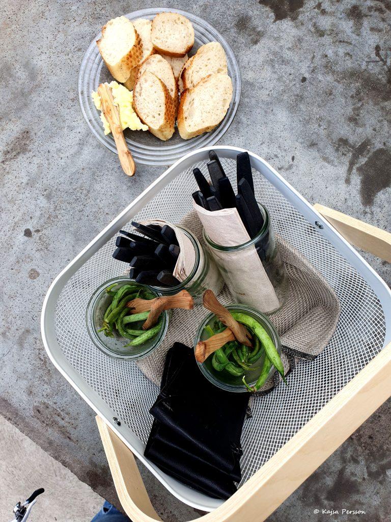 Vit picknick korg med picklade gröna bönor i glas, två glasburkar med servetter och bestick med svarta handtag samt fyra svarta små skinnväskor. Bakom picknick korgen på bordet står ett fat bröd med smör.