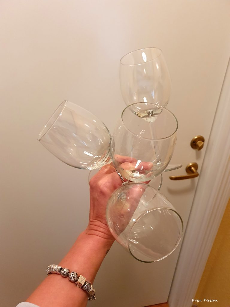 Hand med fyra tomma vinglas framför en dörr