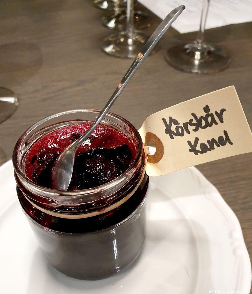 En burk med röd marmelad med en handskriven lapp med orden Körsbär och Kanel