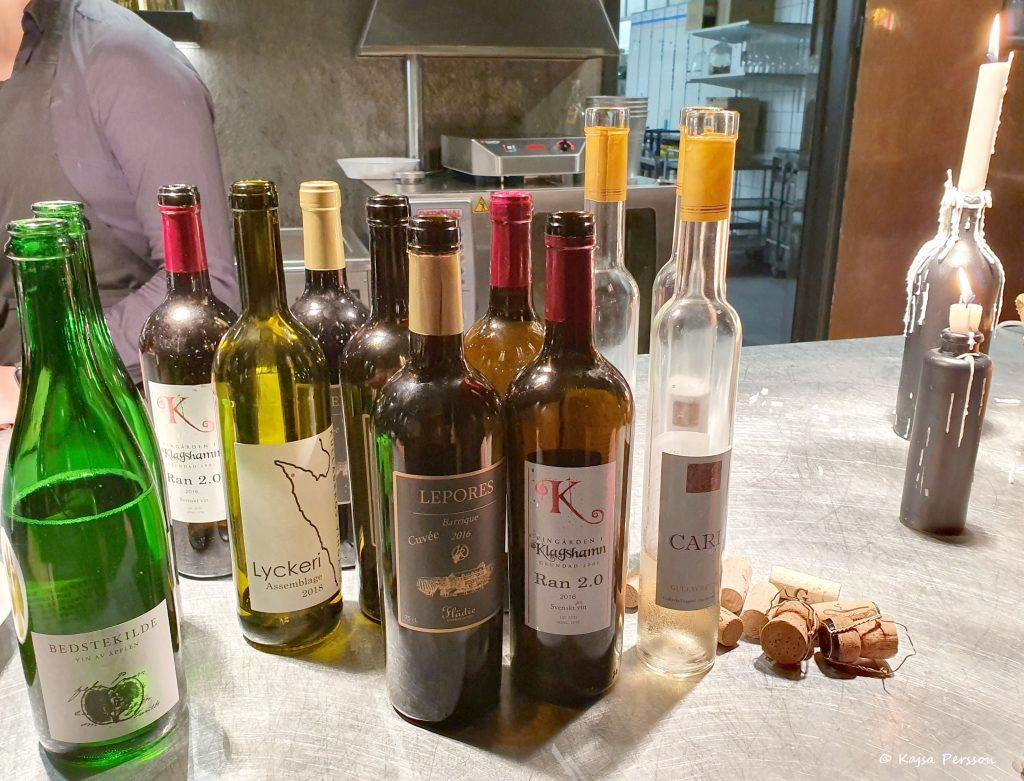 Flera tomma vinflaskor av vinerna som provats under kvällen med vinkorkarna bredvid sig. Två tända stearinljus vid sidan om där stearinet runnit ner på sidorna.
