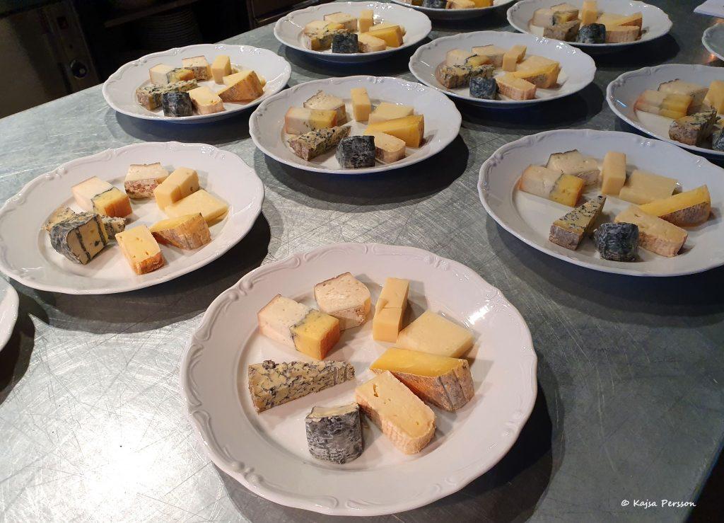 Flera vita tallrika med ostbitar på en alminum bänksiva