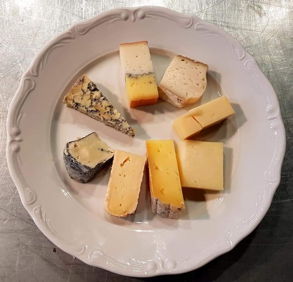 Vit tallrik med 8 bitar ost av olika slag