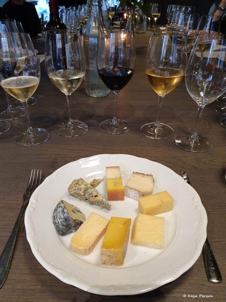 Fyra glas fyllda med vin, tre med vitt vin och ett i mitten med rött vin. på tallriken framför ligger 8 bitar ost av olika slag. Getost, hårdost, kittost och Mögelostar.