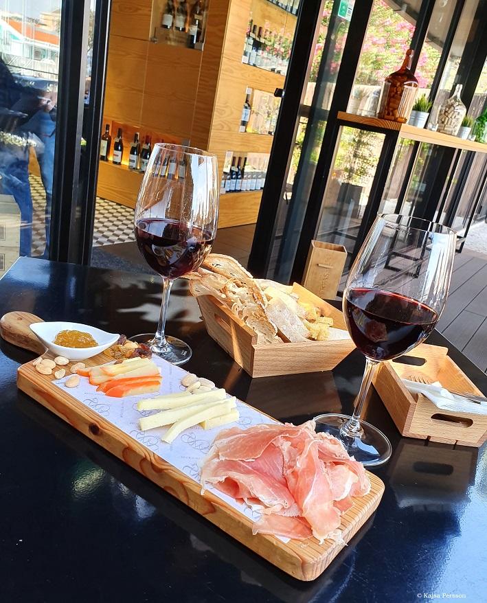Charkbricka med ost och två glas rött vin  i Lissabon