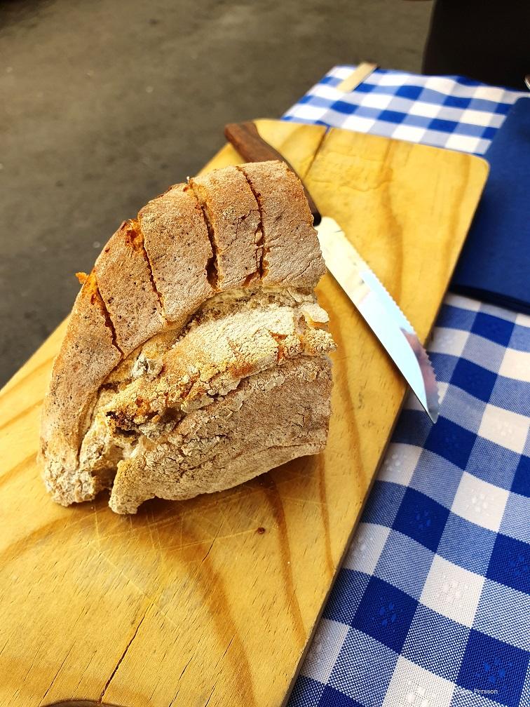 Hembakat bröd på en skärbräda och frågor om mat & dryck