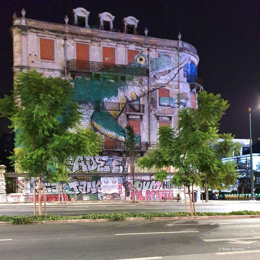 Gatukonst i Lissabon. En stor grön krokodilmålad på fasaden av ett nergånget hus