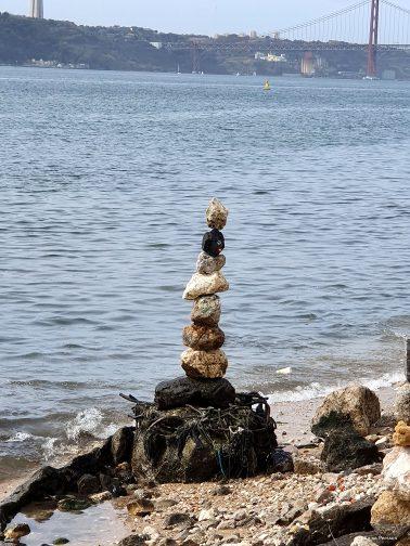 Stenkonst nere vid floden Tejo i Lissabon. Flera stenar staplade ovanpå varandra