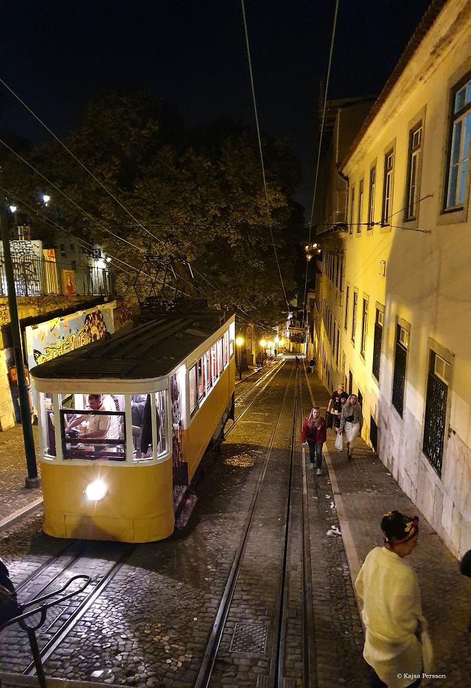 Gul Spårvagn på en bakig gata med kullersten i kvällsbelysning