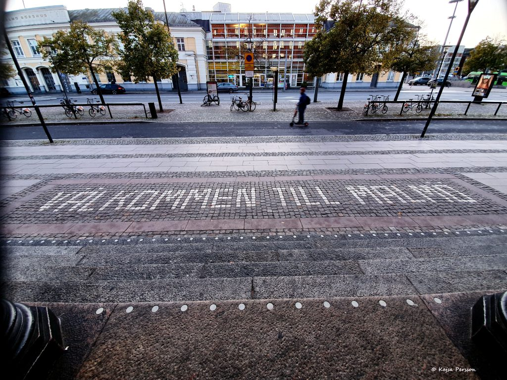 Utanför huvudingången står det välkommen till Malmö med vit gatusten.