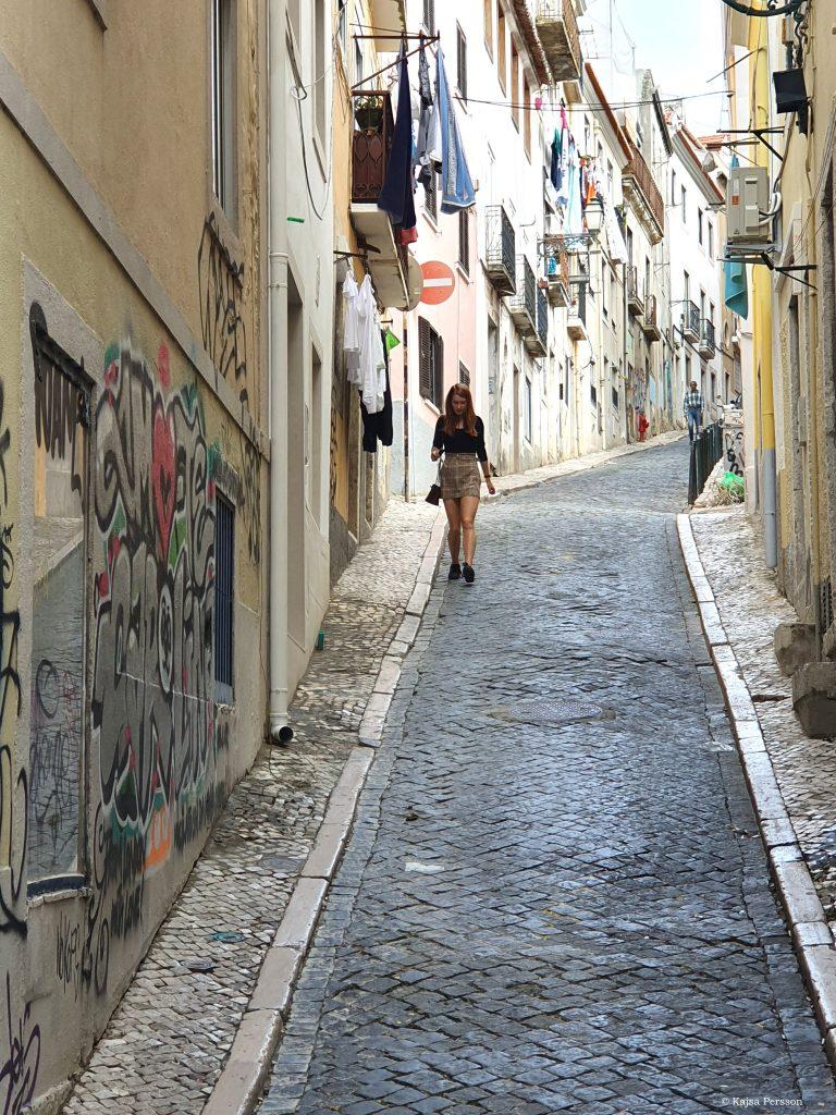 Smal vinglig gata i Lissabon med tvätt hängades från balkongerna
